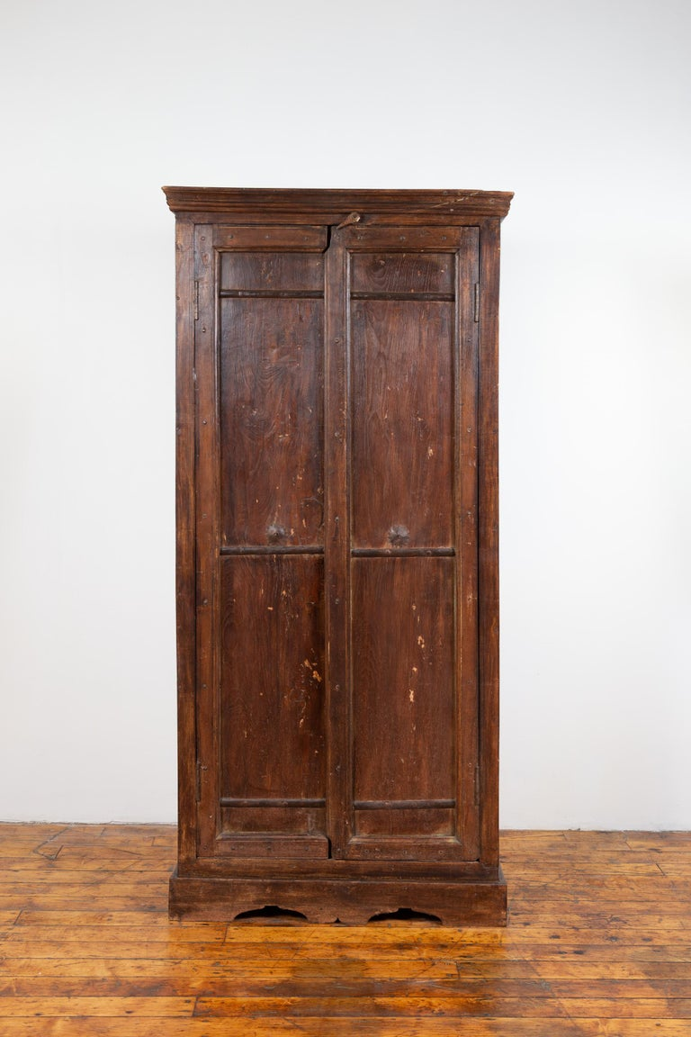 An antique Indian wooden armoire from the early 20th century with paneled doors and interior shelves. Born in India during the early years of the 20th century, this wooden armoire features a linear silhouette, accented with a molded cornice at the