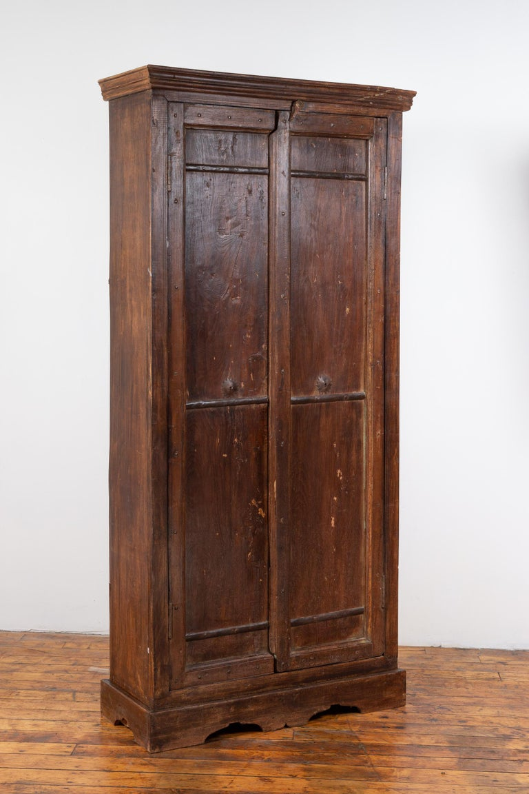 Indian Antique Wooden Armoire with Paneled Doors, Metal Braces and Aged Patina In Good Condition For Sale In Yonkers, NY