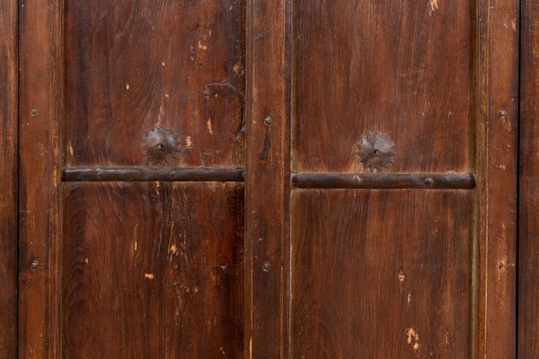 Indian Antique Wooden Armoire with Paneled Doors, Metal Braces and Aged Patina For Sale 1