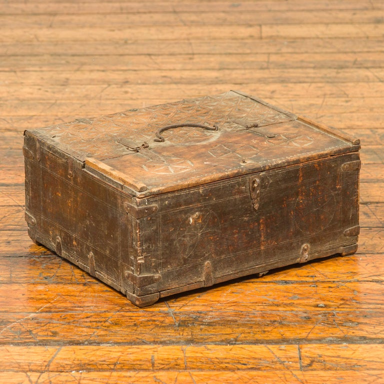 An antiue Indian wooden dowry box used by a merchant, with geometric design. Charming us with its weathered appearance and subtle geometric design, this dowry box showcases a rectangular top carved with geometric diamond and rosette motifs, and