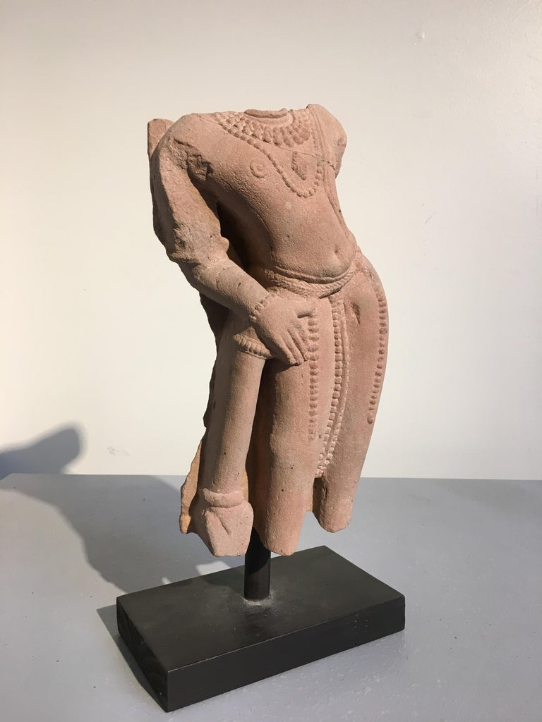 An alluring fragmentary sculpture of the Hindu god Vishnu, carved from pink sandstone, Madhya Pradesh, circa 10th-11th century.  Carved from a pink sandstone, Vishnu the Preserver is portrayed in an exaggerated tribhanga (thrice bent) pose. His