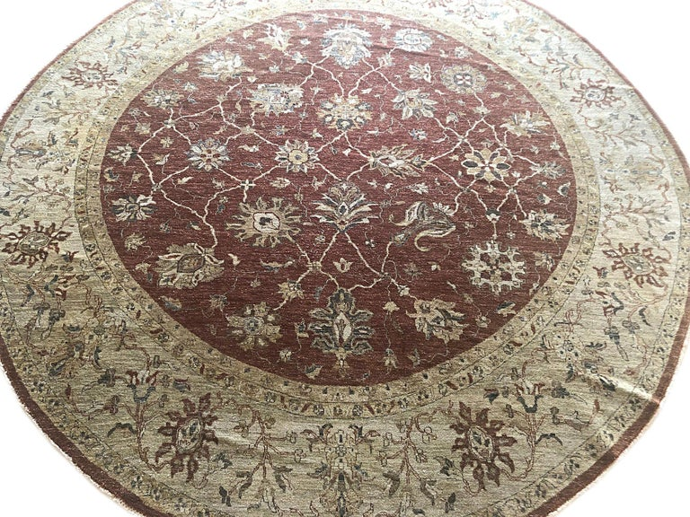 This beautiful round rug is from India and has Peshawar woven style. The size is 11 feet and 8 inches. The design is Mahal. The pile is wool and the foundation is cotton. This rug has a very small re-weaving on one side. This is a pre-owned rug.