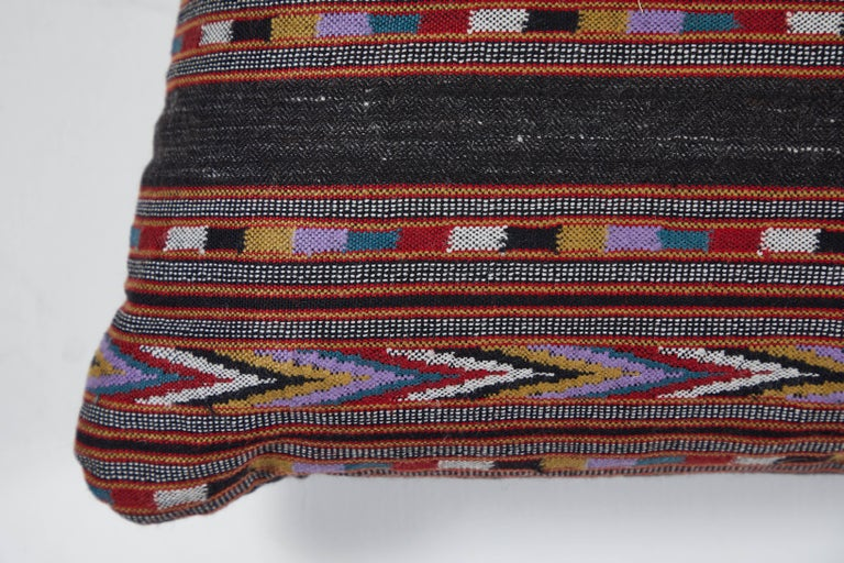Handwoven yak wool with decorative brocade details. Red, ivory, yellow, black and violet. Black linen back, invisible zipper closure and feather and down fill.