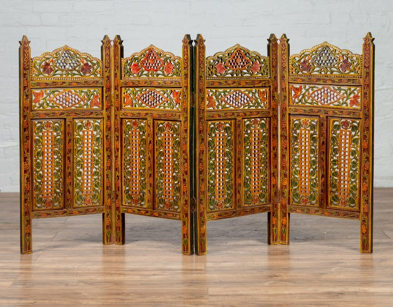 A petite Indian vintage multi-color open fretwork four-panel screen, hand carved and hand painted. Born in India during the midcentury period, this small and exquisite screen features four folding panels, each adorned with a mesmerizing décor of