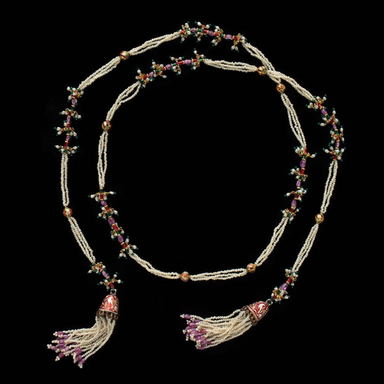 A stylish and colorful 14k gold necklace Mughal style lariat, circa 1950's,  designed with seed pearls and accented with red, green and white enamel, and sapphire beads. Overall length is 42
