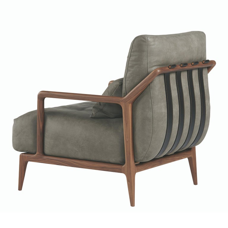 A classic design with a modern twist, this bold armchair will complement a broad variety of interiors with its cosmopolitan flair. Crafted of solid Canaletto walnut with a squared, open frame, the back is supported by leather straps that run