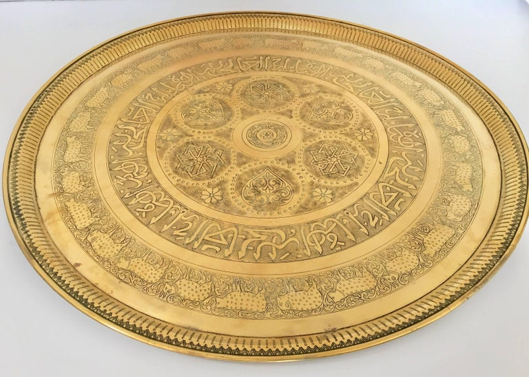 Large handcrafted decorative Indo-Persian brass tray. Embossed and hammered with floral and mystique animal scenes with Arabic calligraphy repousse writing. Large decorative hanging platter with pie crust edges. Great for outdoor use as well, use