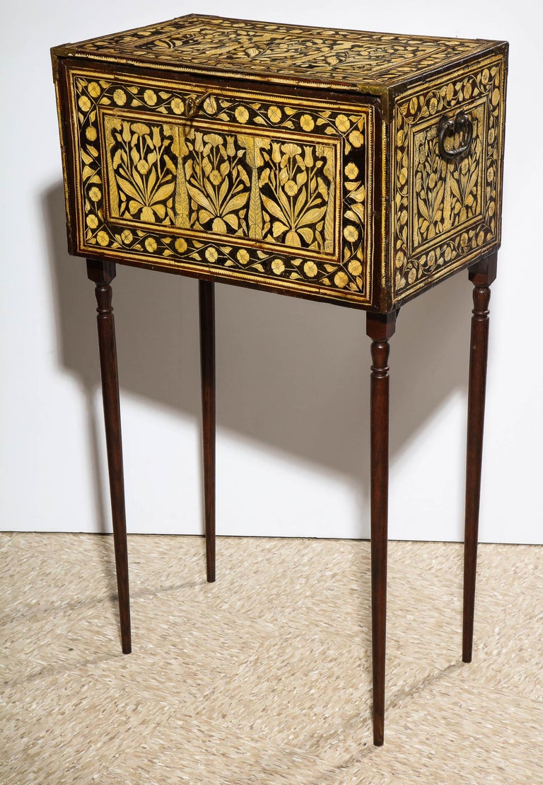 An indo-Portuguese bone-inlaid fall front cabinet / box on stand, Mughal, India, 17th-18th century  With hinged drop-front opening to reveal nine drawers, metal lock plate and key frame inside, handles on each side  wood inlaid with