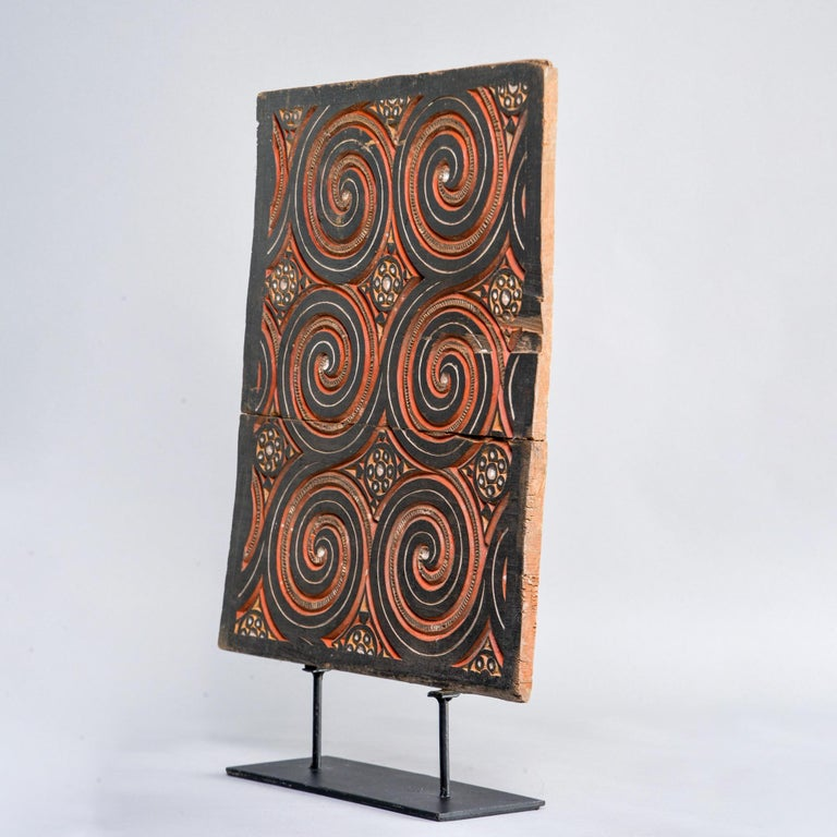 Circa 1930s carved and painted Indonesian wooden panel on black iron display stand.