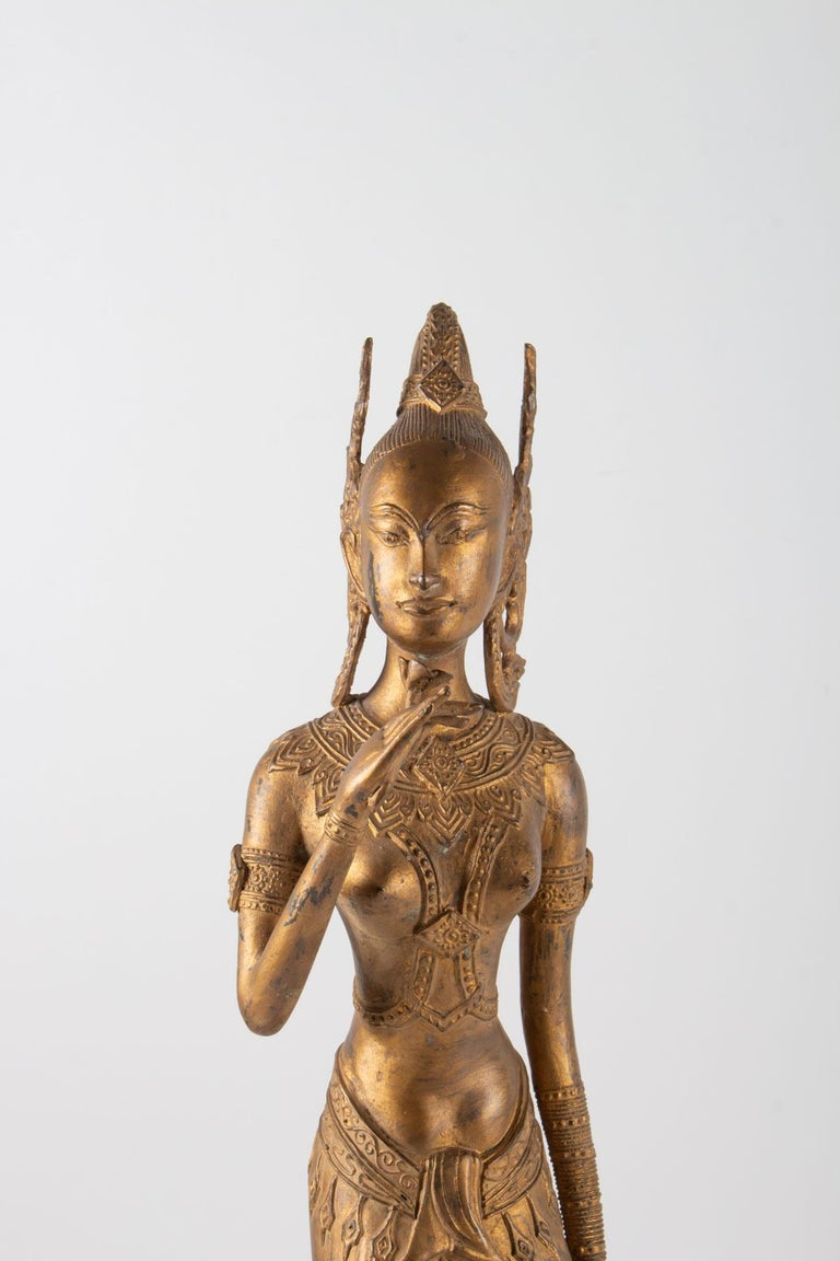 Indonesian goddess in gilded metal holding a lotus flower, 1920-1940. Measures: H 61cm, W 15cm, W 15cm.
