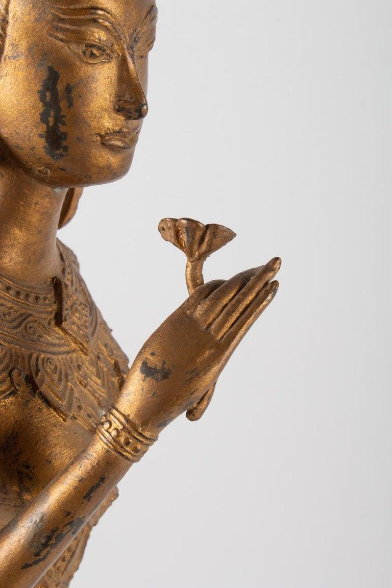 Gilt Indonesian Goddess in Gilded Metal Holding a Lotus Flower, 1920-1940 For Sale