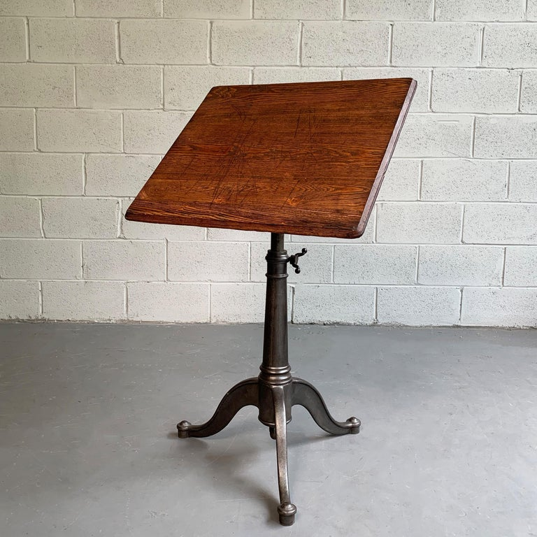 Small, antique, artist rendering easel table features an oak top on a tilt and height adjustable, cast iron, pedestal base that adjusts from 29 - 40 inches height.