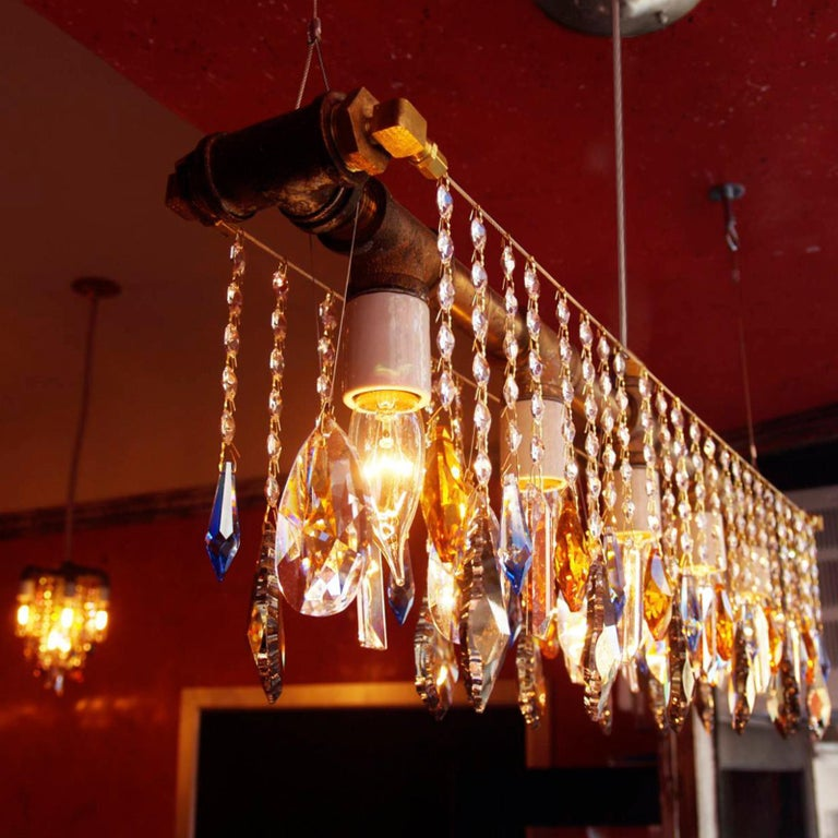 A classic. This version of theindustrial bar chandelier linear suspension features a brass finish and Swarovski colored accent crystals in addition to five porcelain sockets in a straight-line across a structure made of rough industrial pipes and