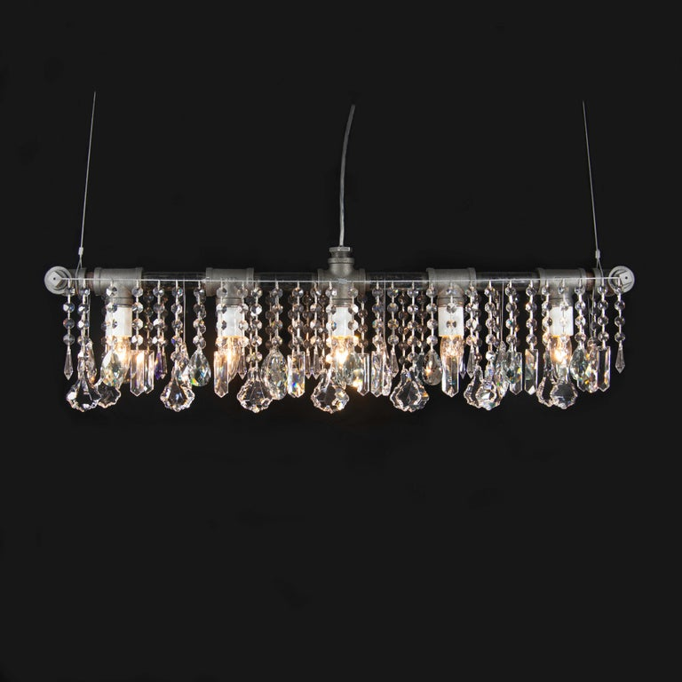 A Classic. This Industrial bar chandelier linear suspension features five porcelain sockets in a straight-line across a structure made of rough industrial pipes and fittings and flanked by curtains of super-high quality crystal, hanging from taut
