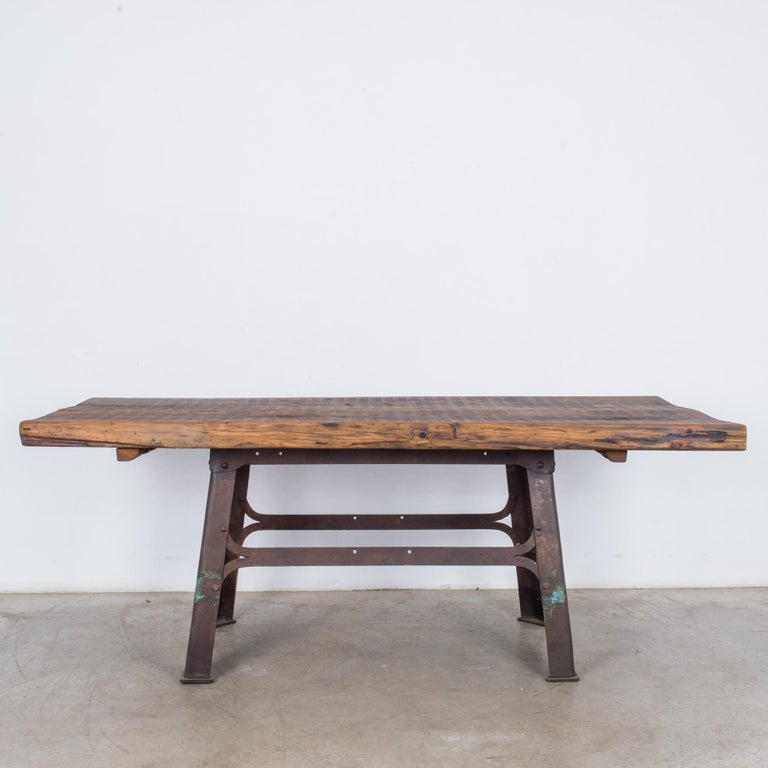 A table from Belgium, circa 1900, with a metal base and wooden top. Legs of metal girders, set at an A-frame angle, make an industrial contrast with the organic swell of the tabletop; a rustic wooden slab, marked by soft undulation and a dark grain.