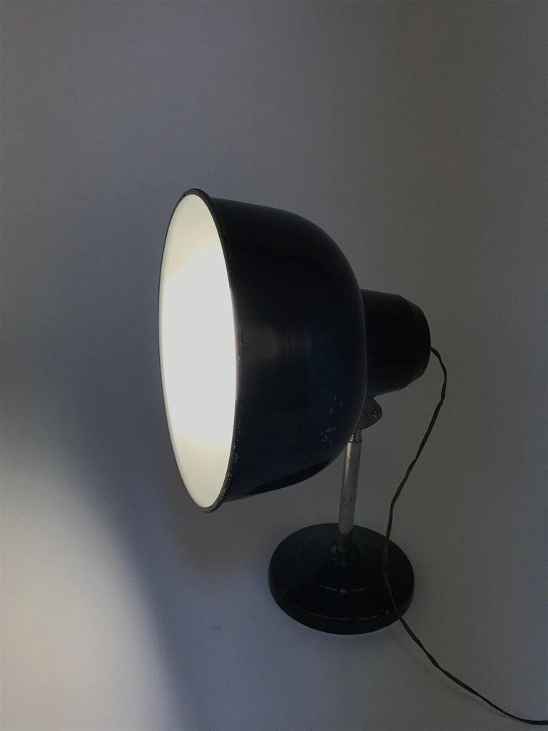 Amazing midcentury industrial black enamelled metal adjustable table desk lamp. This fantastic item was designed in Italy during the 1940s.  This marvellous lamp has its original bulb from the 1940s at 125 volts. Works with 250-volt bulbs, but