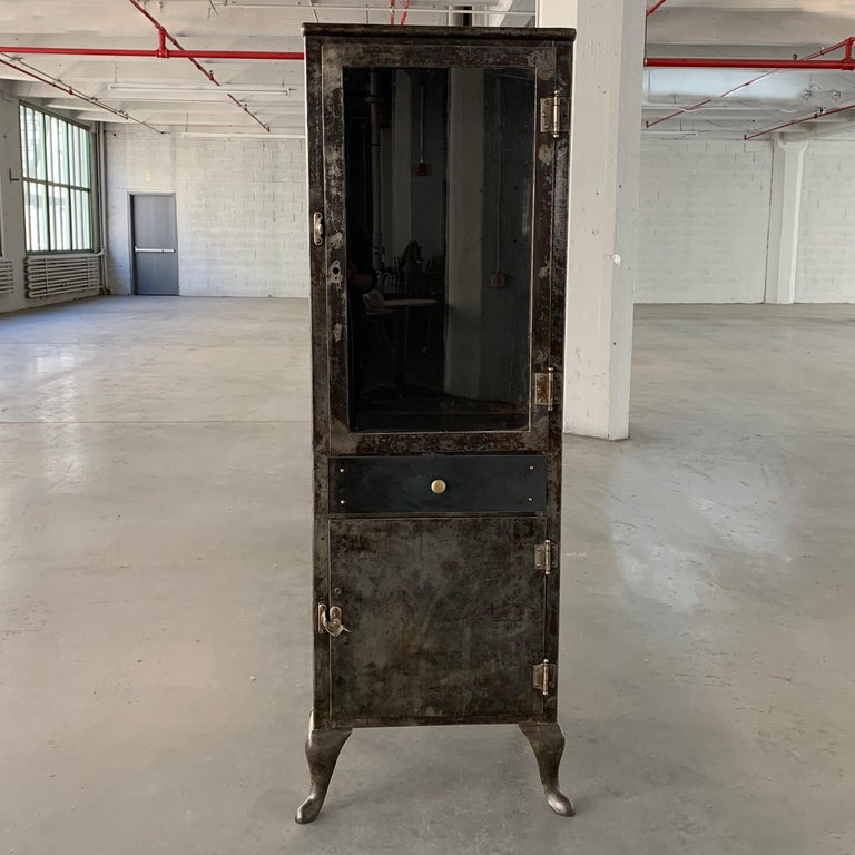Early 20th century, industrial, brushed steel, apothecary cabinet features glass front, display on top that measures 31.5 inches height inside and closed storage below. 2 glass shelves are included for the top interior.