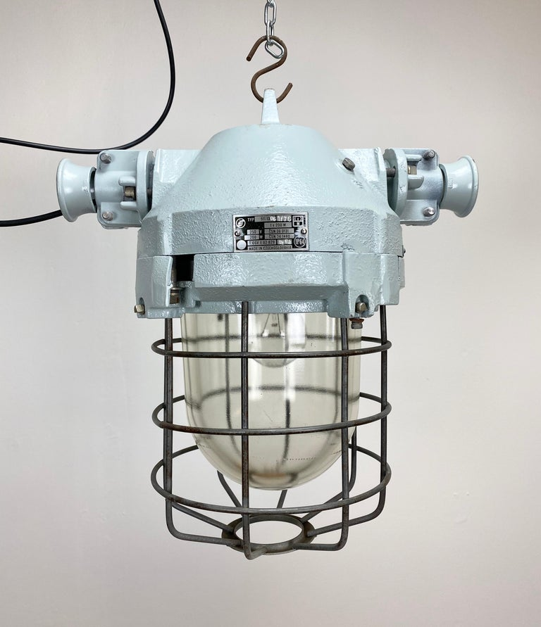 This industrial light was manufactured in former Czechoslovakia by Elektrosvit in the 1970s. It has a cast aluminum body, an iron cage and explosion-proof glass. It weighs 9 kg and has been rewired.