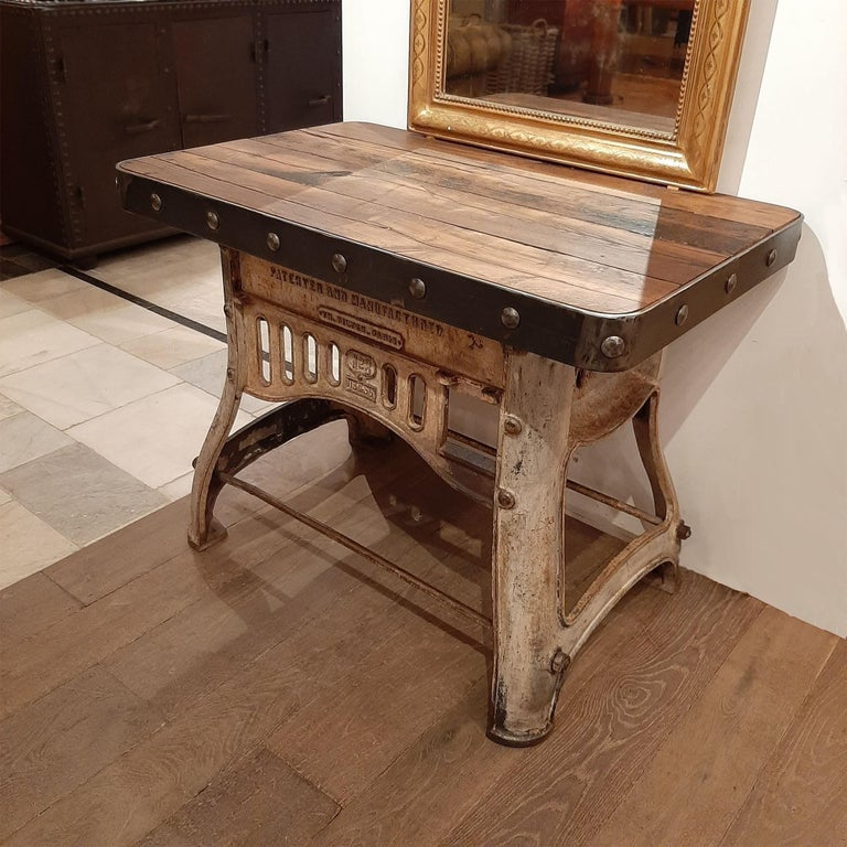 A robust industrial workbench to be used as sidetable or sideboard. This beautiful piece is newly made out of very old industrial materials; an old cast-iron base and a top made of antique oak wagon parts, finished with a sturdy steel