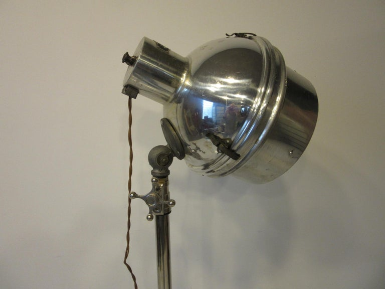 A industrial nickel chrome-plated adjustable floor lamp a large lamp head with a mercury toned reflector behind the bulb, big stylized knobs and great scissor base with built in feet to protect your floors. Has the repro old school looking