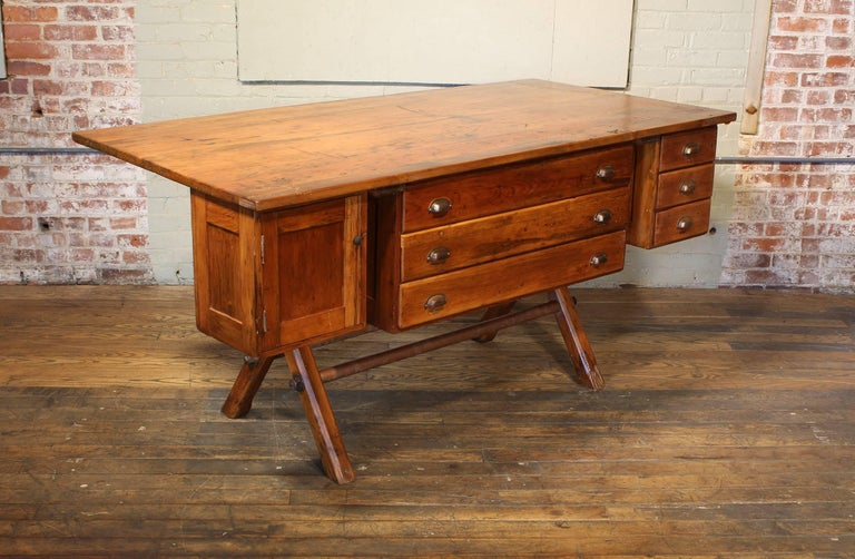 Authentic vintage industrial style wooden desk, workbench, work table, made from pine and steel. Features six drawers and one cabinet with door. Measures 74 1/2