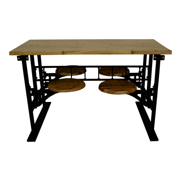 This industrial table with seating features a reclaimed butcher block top, maple seats, and a cast iron frame. Large screws were used to secure the wood to the frame and complete the Industrial look. The set was designed as a replica of factory and