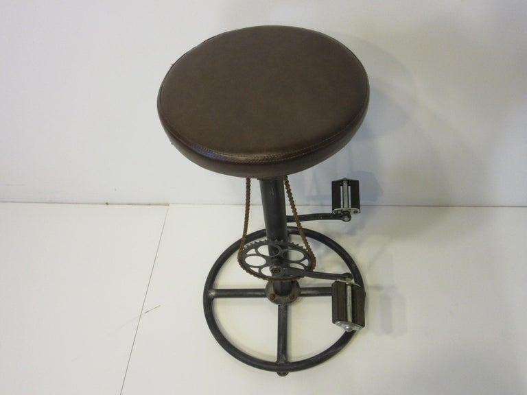 A fun Folk Art industrial stool with painted metal base and shaft having swiveling leatherette seat and a bicycle sprocket, chain and fixed pedals as foot rests. A nice unique piece for that corner of the kitchen, office or bar area.