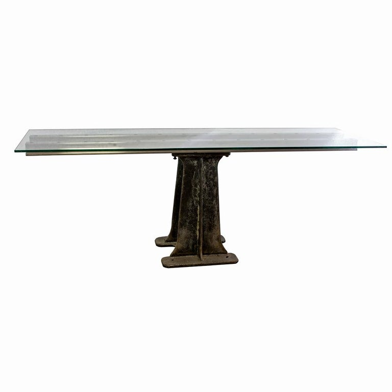 Smooth, sleek, and modern, this iron and glass table combines the contemporary with the antique. A salvaged iron machine base pairs beautifully with stainless I-beams and a thick glass top for a table that is subtle and striking.