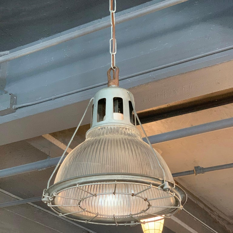 Single, industrial, factory pendant light features a Holophane glass shade within a steel cage frame with porcelain mogul socket. The pendant is newly wired to accept up to a 200 watt mogul bulb or a medium socket bulb with included adaptor and