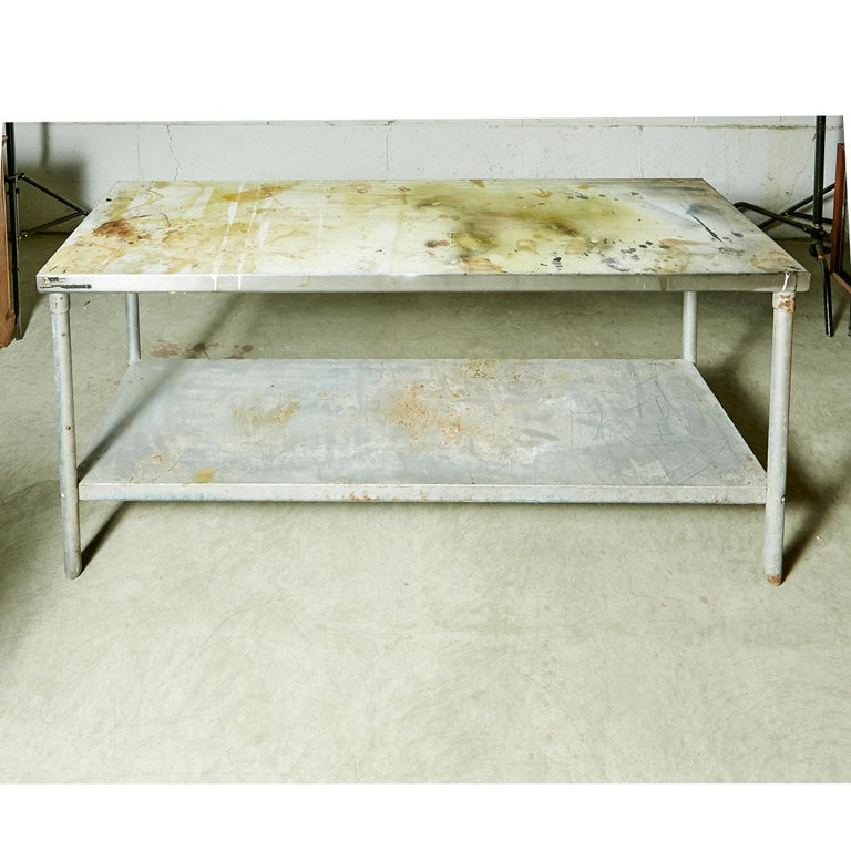 Vintage industrial heavy metal rectangular commercial table with a bottom storage shelf. Table has been used for industrial purposes. Partial label.