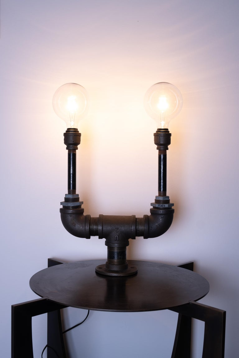 Industrial table lamp by Edelman New York. Made from uniquely sourced, recycled metal piping and fixtures.   - ) Designed and handmade by Female Founded Design Firm  - ) Made in the USA - ) Repurposed materials  - ) Dimmable Globe Bulb (Not