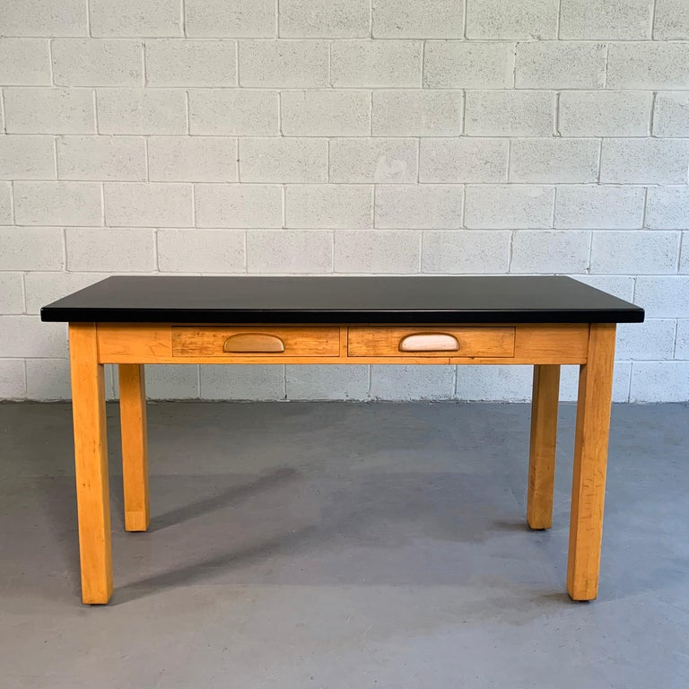 Midcentury, industrial, laboratory table features a 2 drawer, maple base with black, acid-resistant composite top for experiments. At 30.5 inches height, this work table makes a great desk, console, media table or slender dining table. The leg room