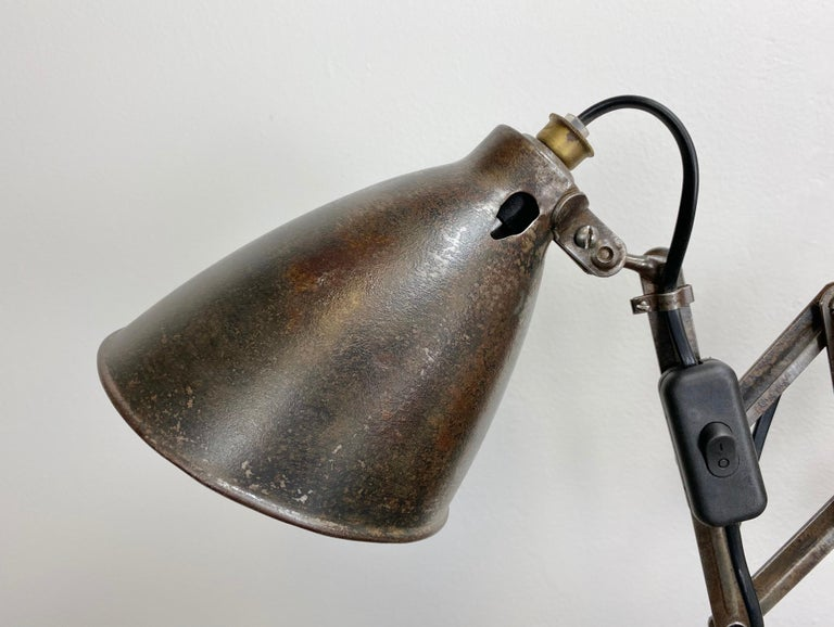 Industrial scissor wall lamp manufactured during the 1950s. The lamp has a metal shade. The iron scissor arm is extendable and can be turned sideways. It has socket for E 27 light bulbs and new wire. Fully functional. Nice patina. Measures: Scissor