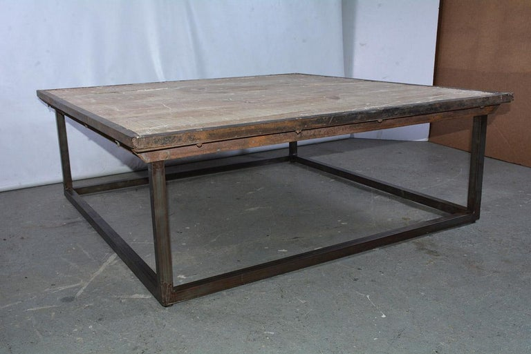 Tabletop is made from salvaged wood pallet that sits on a new iron base cocktail table. Sturdy and rugged, perfect for a loft or Industrial style interior. The combination of the Industrial and contemporary metal base makes this table a modern mix