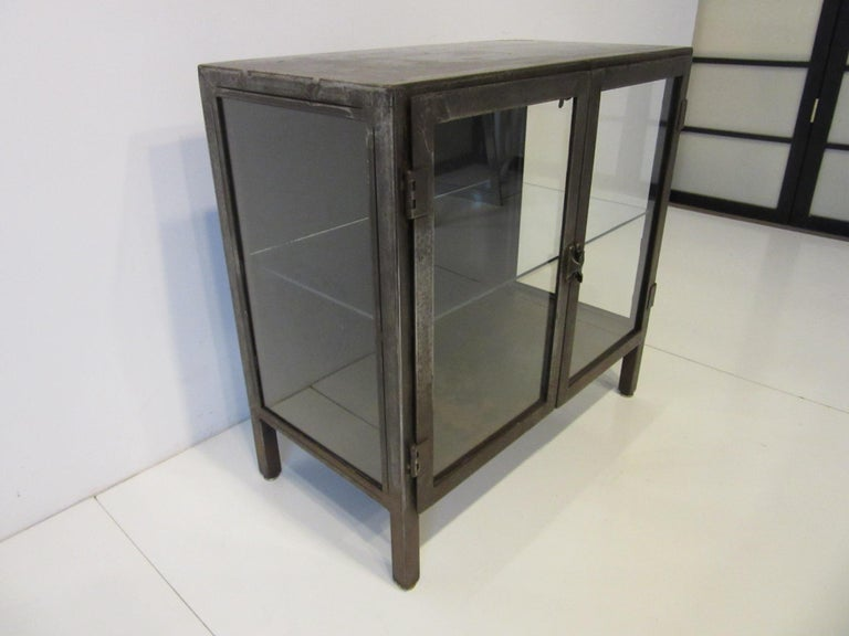 A smaller sized Industrial styled steel display cabinet / bookcase with glass sides and front having two doors a turn latch and one non adjustable shelve. The striped and patina surfaces give the piece a raw and warm look ready for your bathroom,