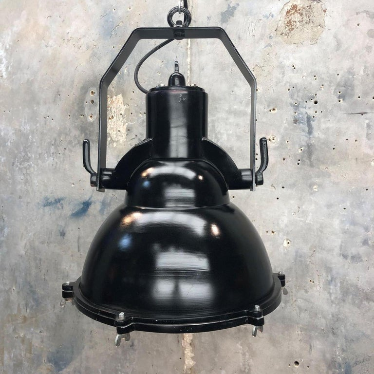 An industrial style black cargo ceiling pendant light.   Reclaimed from military ships and professionally restored by Loomlight in UK ready for modern interiors.   The dome is made from spun aluminium and the hanging frame is cast aluminium. It