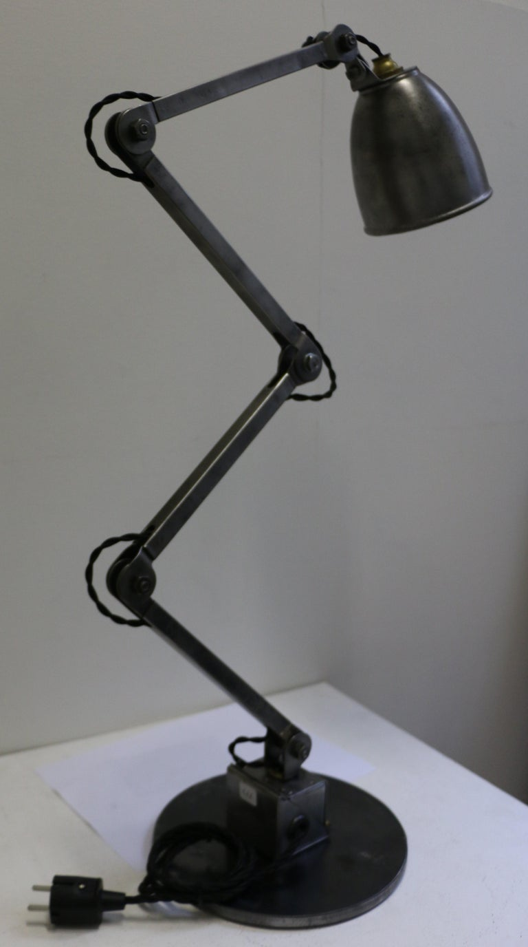 Industrial table lamp manufactured by E.D.L. circa 1950. This articulated steel lamp has been remounted on a round steel plate. Steel has been polished. It can be oriented in multiple positions. Very good condition. It has been rewired for European