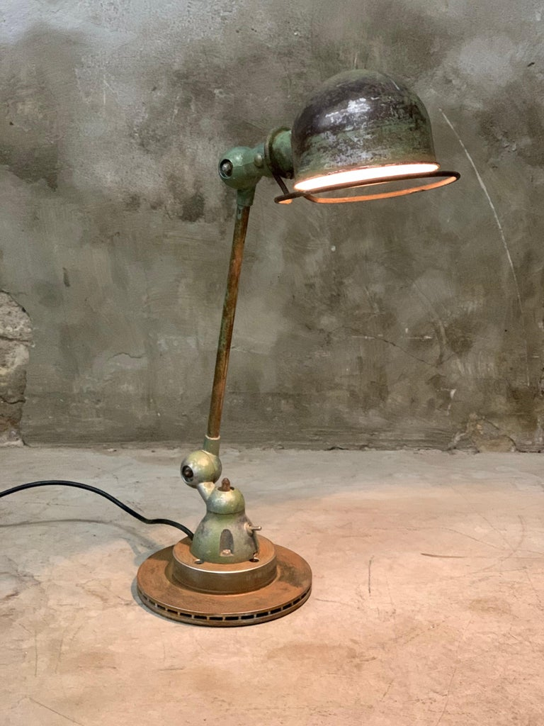 Industrial lamp by Jean-Louis Domecq for Jieldé, France, 1960s. This original old Jieldé table lamp has a fantastic patina! Bayonet lamp fitting including lamp (can still be ordered if it breaks). Placed on an old brake disc.   Flip switch in the