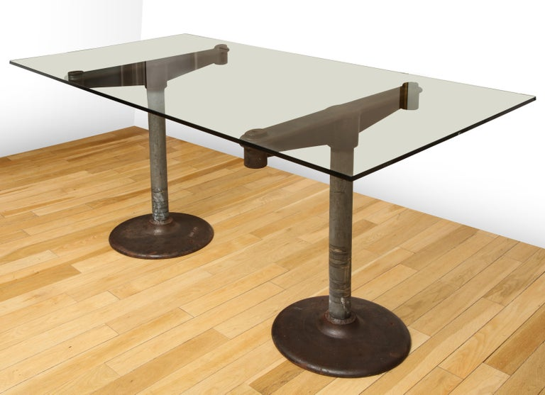 Industrial iron base table with 5' glass top from the 1950s. Supports are two separate pieces.