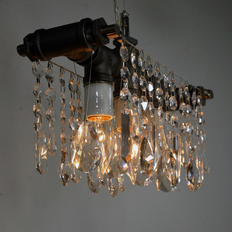 Theindustrial three bulb chandelier is a crystal lighting fixture that may be small but has an oversized personality. It gets the Michael McHale Designs formula of polished European crystals contrasting with rough industrial elements exactly right.
