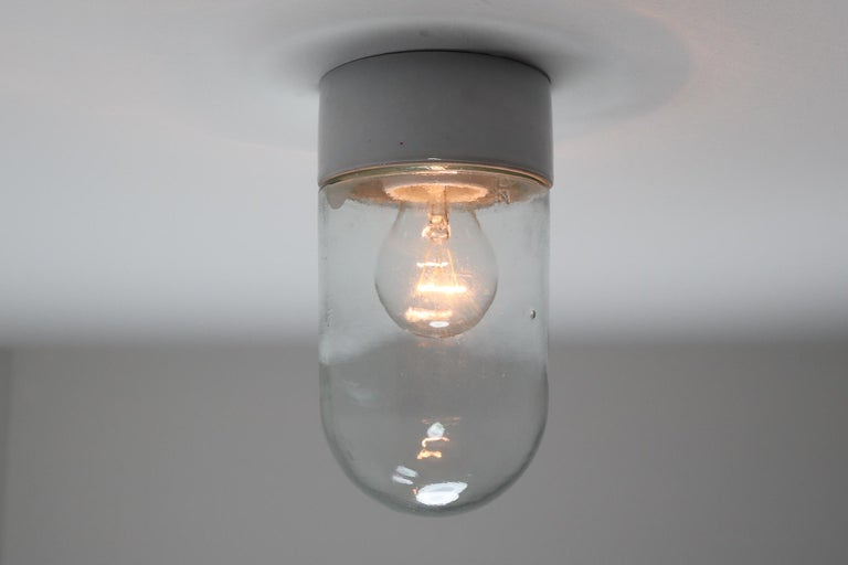 Small industrial vintage modern wall/ceiling lights with clear glass and porcelain base, France, 1960s. Good original condition. Fitted with a porcelain E27 socket. The lights are compatible with the US/UK/ etc., standards. Also LED compatible. 2
