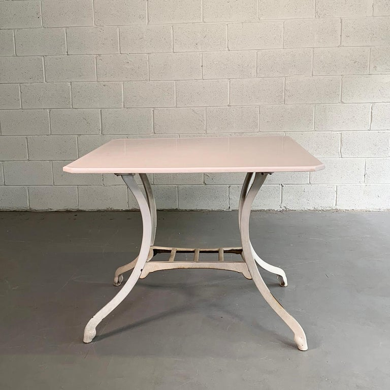 Industrial, early 20th century table features an enameled, cast iron base with milk white, Vitrolite top.