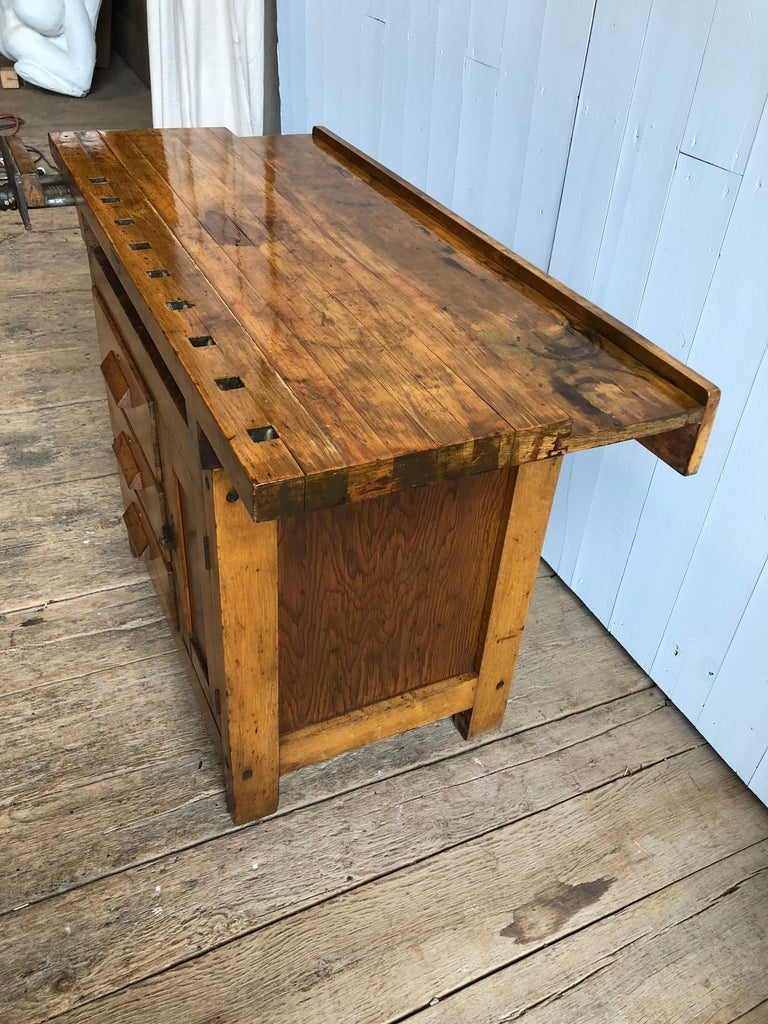 An unusual small size industrial work bench circa 1930 in maple, with a butcher block top, a vice clamp, 3 large drawers and a storage cabinet. Would be perfect for a small bar - trays can be stored in the space under the top, bottles in the cabinet