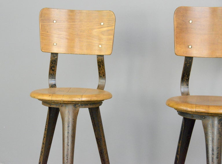 Industrial work stools by Ama, circa 1930s  - Price is per stool - Steel frame - Solid elm seat with ply backrest - Designed by Albert Menger  - Produced by Ama, Nordhalben - German, 1930s - Measures: 35cm wide x 41cm deep  - 56cm seat
