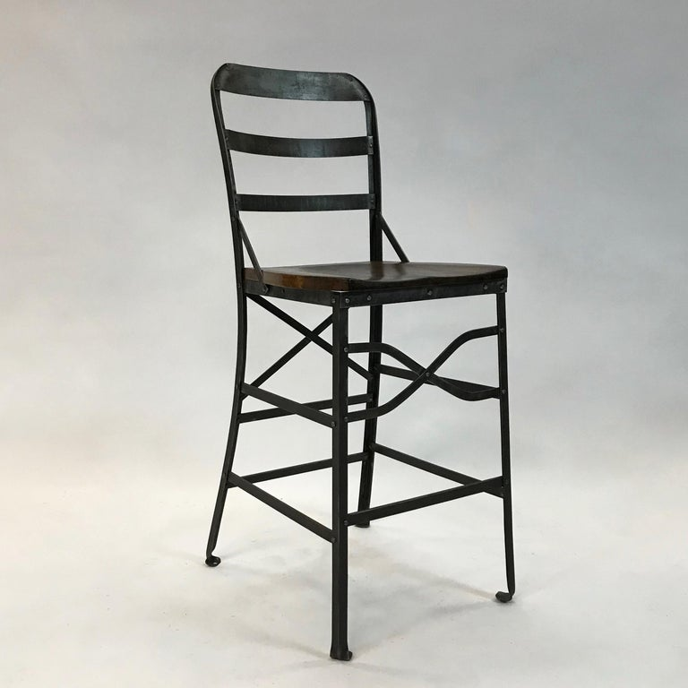 Industrial, counter height, shop stool features a wrought iron frame and contoured oak seat.