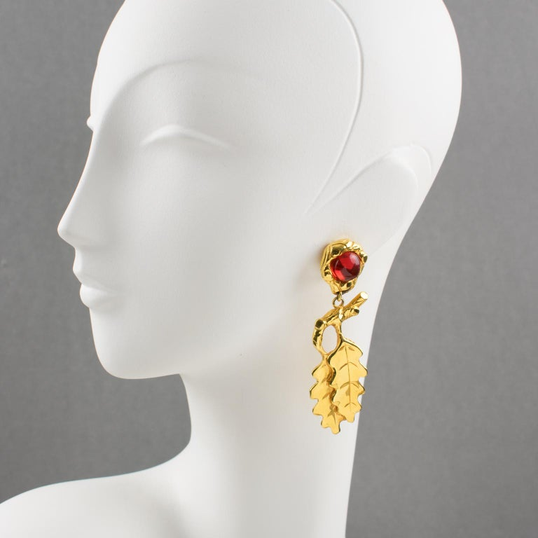 Oversized clip-on earrings by Ines de la Fressange Paris. Dangling shape, with gilt metal all carved and textured featuring oak leaves compliment with amber resin cabochon. Signed underside with Ines de la Fressange gilt logo tag: