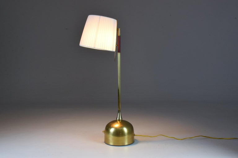 Contemporary handcrafted articulating table lamp designed in a gold polished brass stem which articulates at the brass base with a pear-shaped joint.  The Flow collection is an ode to movement designed by Jonathan Amar composed of artisanal