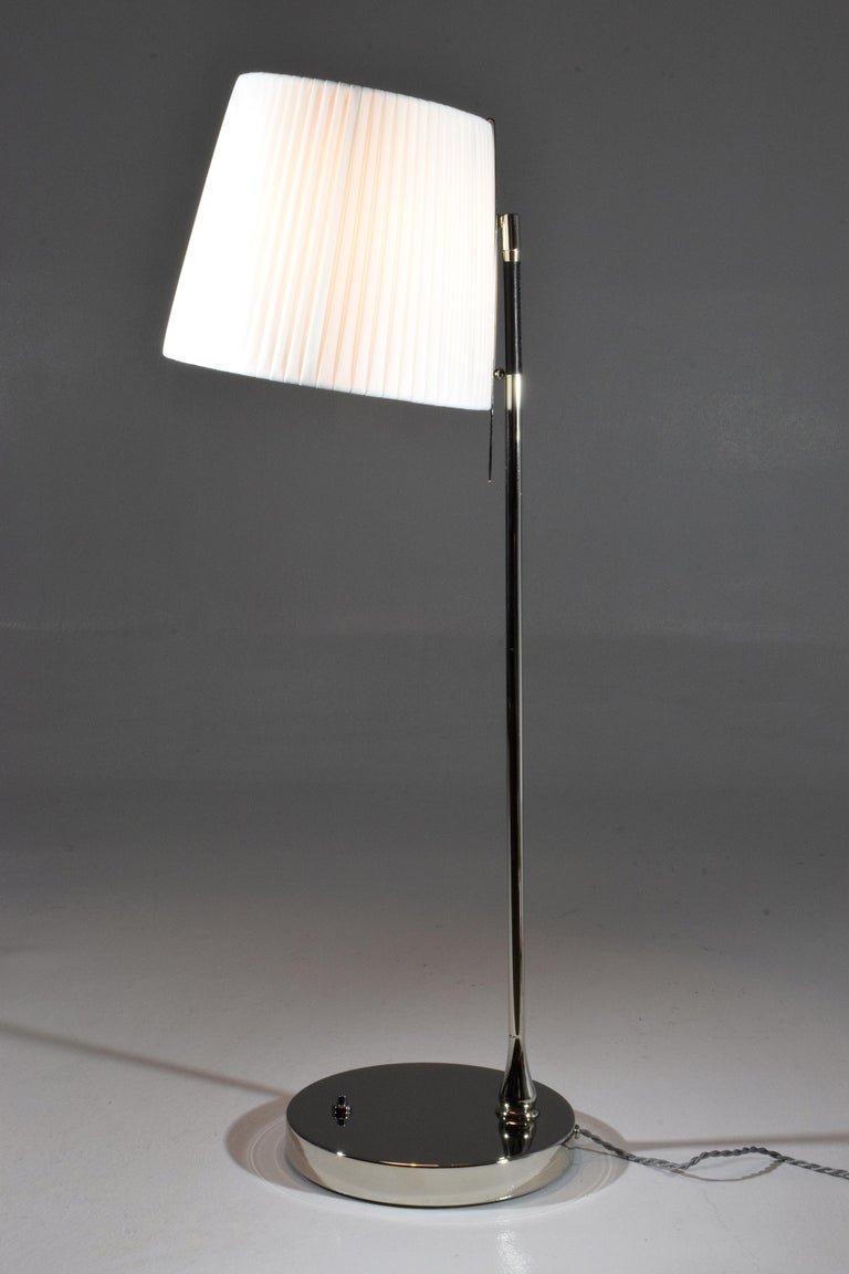Contemporary handcrafted tall table lamp composed of a nickel-plated solid brass structure and adorned with a black hand-sewn sheathed leather detail. The fabric shade rotates at 90 degrees and is designed with a stem so you may orientate the light
