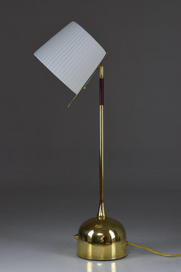 Contemporary handcrafted articulating table lamp pictured in a solid polished brass finish, adorned with a dark red hand-sewn sheathed leather detail by artisan saddle makers. The lamp is designed with our signature pear shaped joint and the