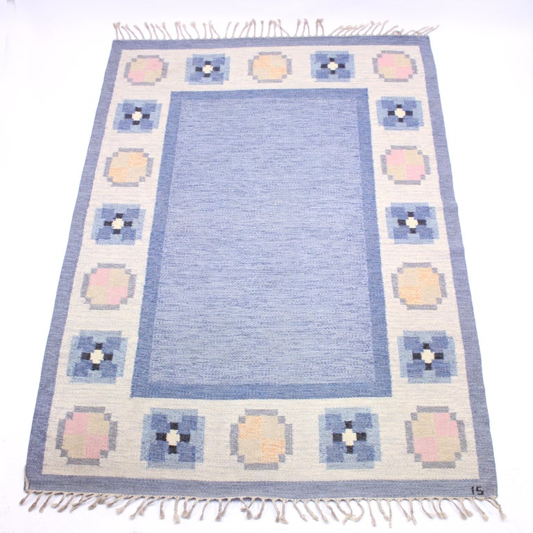 Flat weave Röllakan carpet designed by Ingered Silow in the 1950s. Main colours are blue and white with a dose of pink, black and yellow. Newly cleaned by a professional carpet cleaning company. Very good vintage condition with minimal ware